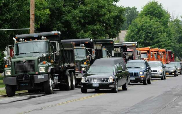 A hearse passes by a motorcade of town highway vehicles from White Creek and nearby towns as they head to the cemetery from the Cambridge United Presbyterian Church in Cambridge, N.Y. July 18, 2011, after the funeral of Dan Harrington, Deputy Town Highway Superintendent for the Town of White Creek, his wife Lisa Harrington and step son Josh O'Brien who were shot to death and their bodies burned allegedly by their son Mathew Slocum.  (Skip Dickstein / Times Union) Photo: SKIP DICKSTEIN / 2011
