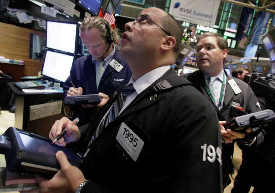 Trader Jeffrey Vazquez, center, works with colleagues on the floor of the New York Stock Exchange Monday, July 18, 2011. (AP Photo/Richard Drew) Photo: Richard Drew, STF / AP
