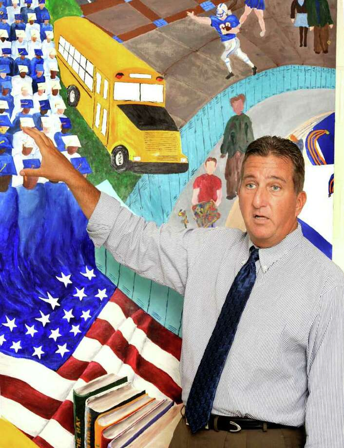 Dr. Bob Rossi is shown in front of a mural that was outside the Danbury High School cafeteria. Rossi resigned over the weekend. Photo: Michael Duffy