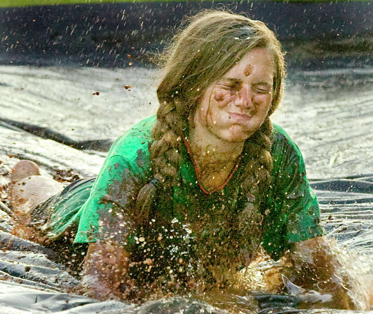 In a Sunday photo, Haley Knable slides through a pool of chocolate syrup, cooking oil and water Sunday at Wesley Memorial United Methodist Church in Decatur, Ala.