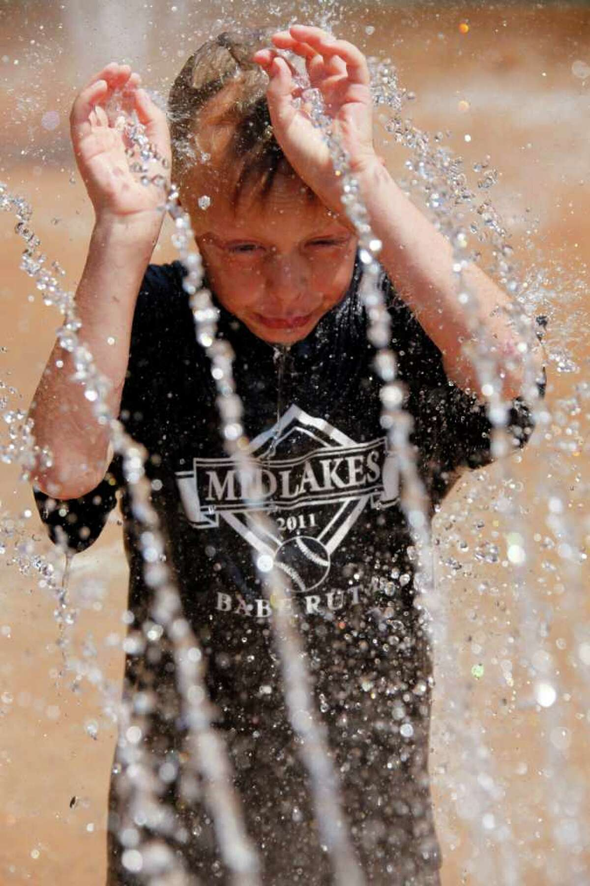 Mason Dziekan cools off playing in a water fountain during the hot summer weather at a park in Batavia, N.Y., on Monday.