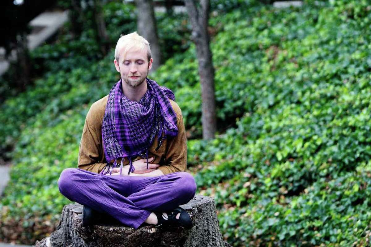 Stephen Fairweather relaxes on a tree stump at the Seattle Buddhist Temple during the Bon Odori Festival on Sunday.