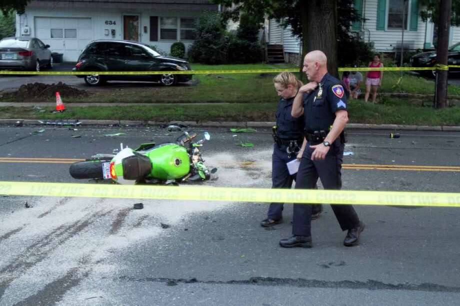Stamford police officers Jessica Bloomberg, left, and Sgt. Carl Strate, right, at the scene of a fatal car versus motorcycle accident on Hope St. on Monday, July 18, 2011. According to Lt. Sean Cooney, the motorcyclist, Fernando Quintero-Montano, sustained serious injuries and was transported to Stamford Hospital. The driver of the SUV which was traveling southbound on Hope was not injured. Police have closed Hope at Viaduct Road. Photo: Chris Preovolos / Stamford Advocate