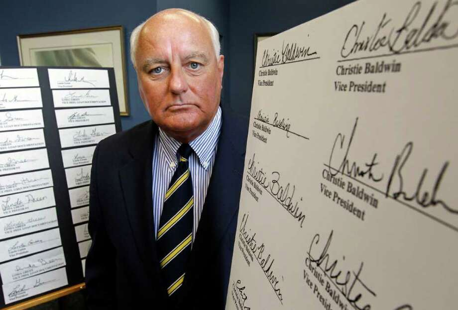 Salem, Mass. Registrar of Deeds John O'Brien stands near copies of robo-signed signatures at his office, in Salem, Monday, July 18, 2011. O'Brien said an investigation of more than 710,000 documents in his office found that 25,187 homeowners in the county, or about 3.5 percent, have paperwork on file with signatures he believes are fraudulent.  (AP Photo/Steven Senne) Photo: Steven Senne, STF / AP