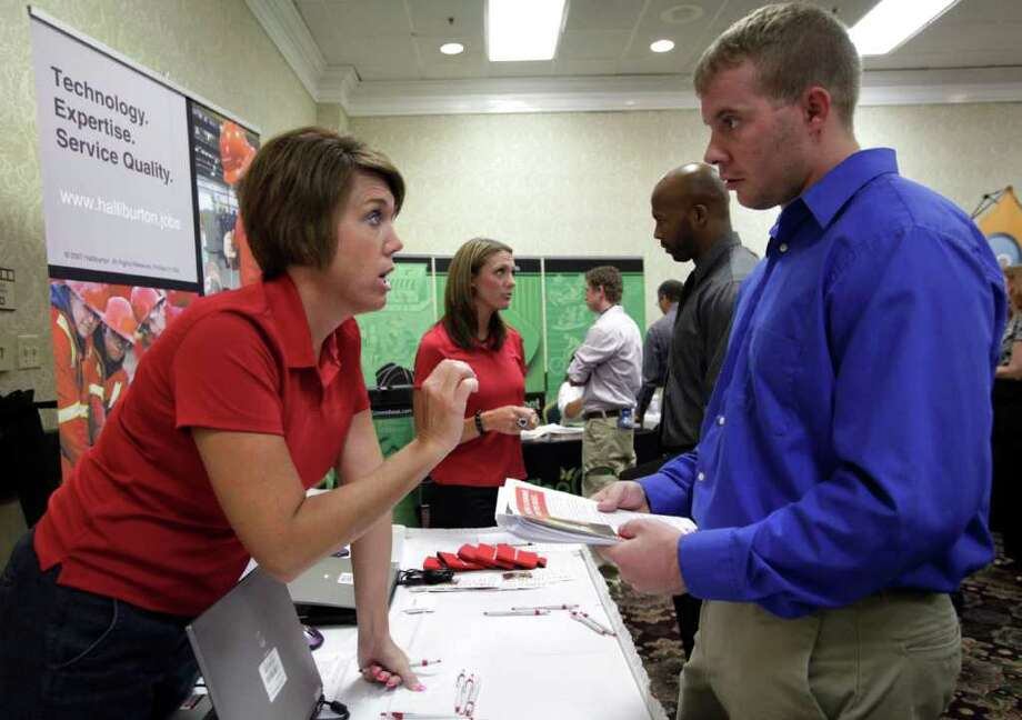 FILE - In this July 13, 2011 photo, Halliburton human resource associates Heather Hopkins, left, and Sonja Franks, center rear, meet with attendees at a National Career Fairs job fair, in Dallas. The expansion of oil and natural gas drilling in North America continued to drive Halliburton Co. as its earnings jumped by nearly 54 percent in the second quarter. Revenue also hit a company record for the period. (AP Photo/Tony Gutierrez, file) Photo: Tony Gutierrez, STF / AP