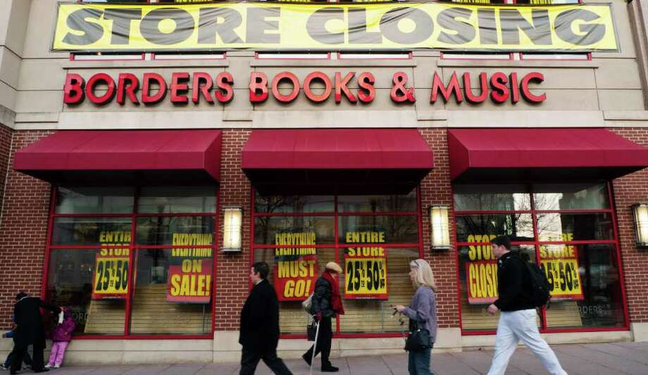 (FILES) This March 4, 2011 file photo shows pedestrians as they pass by a Borders book store with signs announcing that it will be cloing its doors, in Washington, DC.  US book chain Borders is on the brink of liquidation after the collapse of a deal with the Najafi investment firm aimed at saving the bankrupt company, the Wall Street Journal reported on July 14, 2011. At the start of this month Borders had designated Najafi as the opening bidder in a looming bankruptcy court action, but that deal has reportedly fallen through because of objections by publishers and landlords. AFP PHOTO/Mandel NGAN (Photo credit should read MANDEL NGAN/AFP/Getty Images) Photo: MANDEL NGAN, Staff / AFP