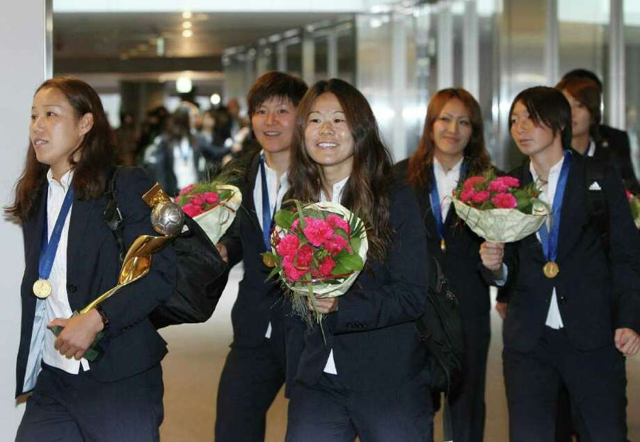 Japanese women's football team members, led by Homare Sawa (C), arrive at the Narita international airport as they returned from Germany at Narita city, suburban Tokyo on July 19, 2011. Japan defeated the US in the final of the women's World Cup football championship on July 17.  AFP PHOTO / JIJI PRESS (Photo credit should read STR/AFP/Getty Images) Photo: STR, - / AFP