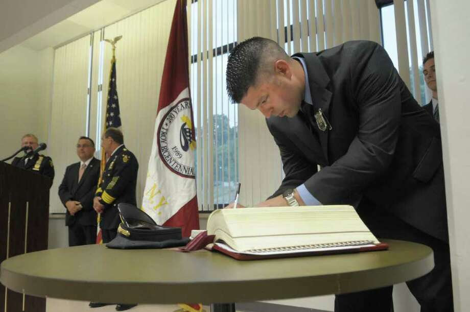 Ryan Davis signs the oath book  during a ceremony to swear in four new city police officers at Troy City Hall on Monday, July 18, 2011 in Troy.  All four officers will be attending the Zone 5 Law Enforcement Academy starting Wednesday, July 20.   (Paul Buckowski / Times Union) Photo: Paul Buckowski  / 00013955A