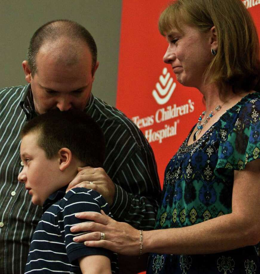 Khris Dysart, left, father, son Keagan, 9, and mother Robin, speak during a presentation on surgery used to help cure Keagan of his epileptic seizures July 18, 2011 in Houston at Texas Children's Hospital. Texas Children's Hospital pioneers used a MRI-guided laser surgery to perform a revolutionary new epilepsy treatment that significantly reduces the risk of patient complications and recovery time, July 18, 2011in Houston. Children's Hospital is the first hospital in the world to use real-time MRI-guided thermal imaging and laser technology to destroy lesions in the brain that cause epilepsy and uncontrollable seizures. A recent example of the effectiveness of this new surgery is nine-year-old Texas Children's Hospital patient Keagan Dysart, of Converse, Texas, who suffered from two types of epileptic seizures when he was diagnosed with a hypothalamic hamartoma in his brain. The gelastic seizure caused him to giggle and laugh uncontrollably two or three times an hour. Keagan would also periodically experience a tonic seizure, with generalized body stiffening and loss of awareness that caused him to fall asleep for sometimes up to an hour afterward. Keaganâs case was particularly high risk because his lesion was located in the hypothalamus, near the brain stem. In this highly sensitive region, there are a myriad of potentially serious complications from surgery including loss of sight, damage to the pituitary gland, stroke from artery damage or development of diabetes insipidus (DI), a potentially fatal condition where the kidneys are unable to conserve water because of disruption to the area of the brain that releases the bodyâs anti-diuretic hormone. (Eric Kayne/For the Chronicle) Photo: Eric Kayne / © 2011 Eric Kayne