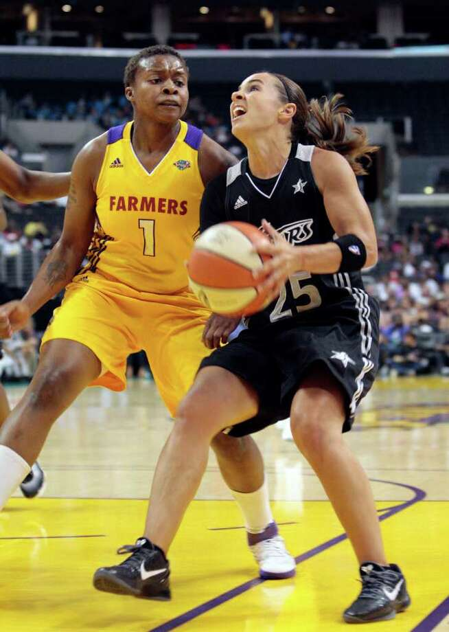 San Antonio Silver Stars guard Becky Hammon, right, looks to shoot as Los Angeles Sparks' Natasha Lacy defends during the first half of a WNBA basketball game in Los Angeles, Monday, July 18, 2011. Photo: Jason Redmond/Associated Press