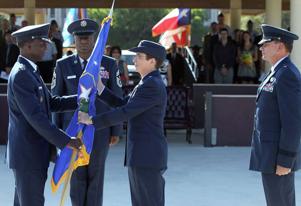 Air Force Brigadier General Theresa C. Carter (center) accepts command of the 502d Air Base Wing Joint Base San Antonio on July 18, 2011 during a change of command ceremony at the MacArthur Parade Field at Fort Sam Houston. Handing over the flag (left) is the event's presiding officer General Edward A. Rice, Jr. and standing on the right is Brigadier General Leonard A. Patrick who is stepping down as commander of Joint Base San Antonio. Standing between Rice and Carter (facing) is Command Chief Juan Lewis.