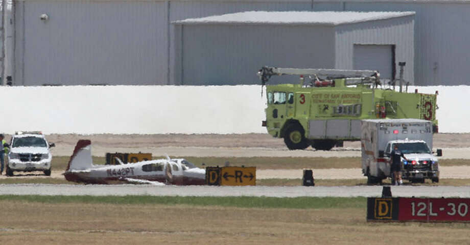 San Antonio emergency personnel surround a small aircraft after it made a hard landing at the San Antonio International Airport, on July 18, 2011. The pilot was hospitalized with back injuries after the aircraft's landing gear failed. Photo: JERRY LARA / glara@express-news.net