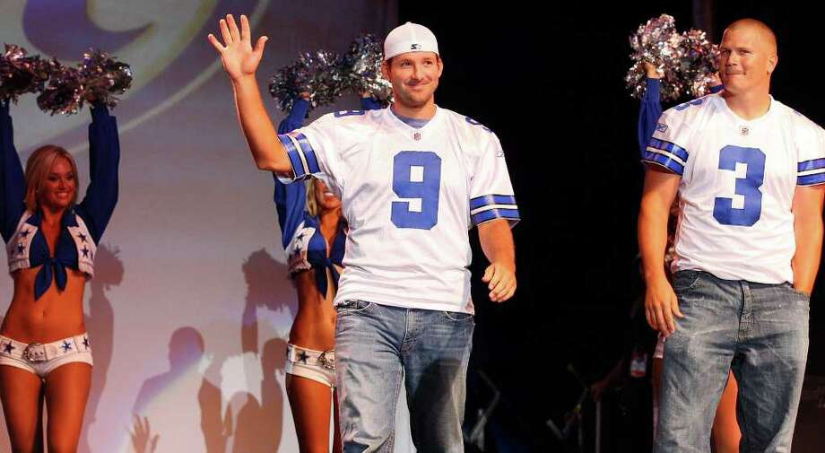 Dallas quarterback Tony Romo waves to fans as teammate Jon Kitna (right) looks on at the Cowboys Kickoff Spectacular last July at the Alamodome. Photo: Edward A. Ornelas/eaornelas@express-news.net / eaornelas@express-news.net