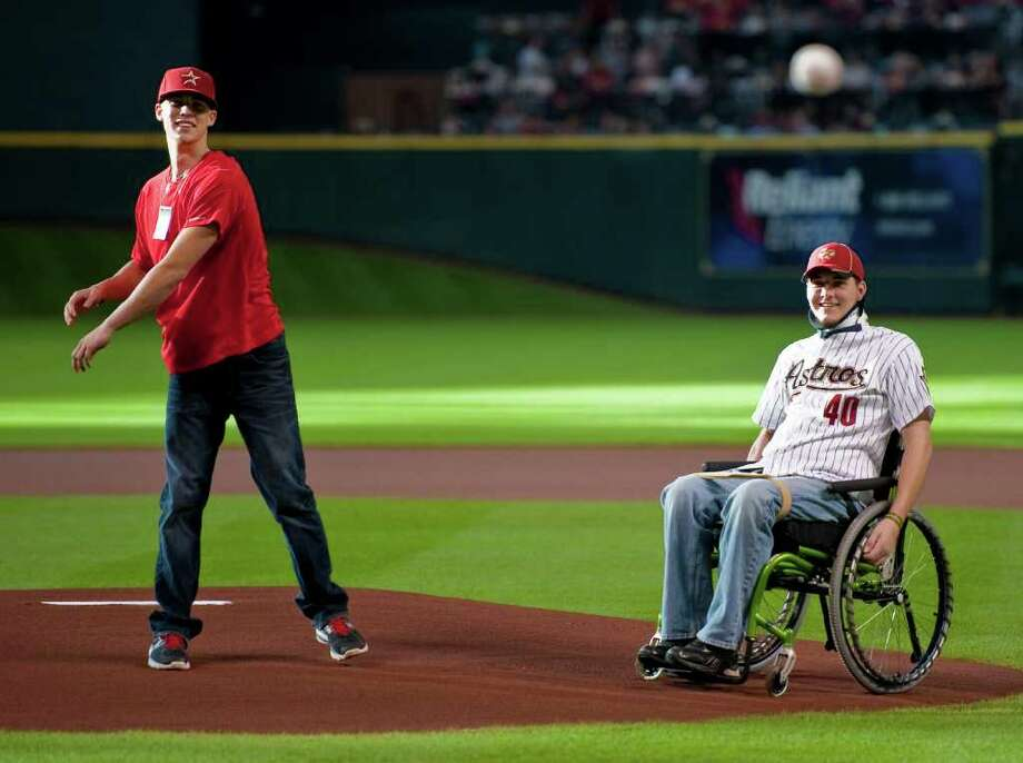 San Jacinto College pitcher Buddy Lamothe, right, watches as teammate Tyler Wright, left, delivers a ceremonial first pitch before a baseball game between the Washington Nationals and Houston Astros, Monday, July 18, 2011, in Houston. Lamothe, a high prospect pitcher, was paralyzed in a swimming accident before the MLB draft but the Astros selected him with their final pick in the draft. Photo: Dave Einsel/Associated Press