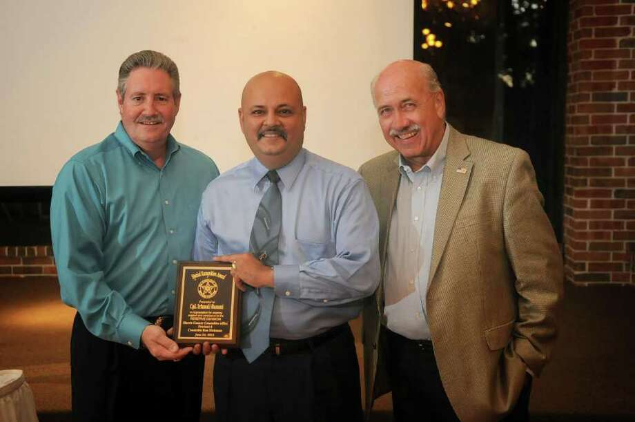 Corporal Irfanali Banani, center, receives his Special Recognition award from Precinct 4 Constable Ron Hickman, left, and Reserve Asst. Chief John Chamberlain during the Twentieth Annual Precinct Four Awards Banquet at Shirley Acres in Houston. Freelance photo by Jerry Baker Photo: Jerry Baker, Freelance