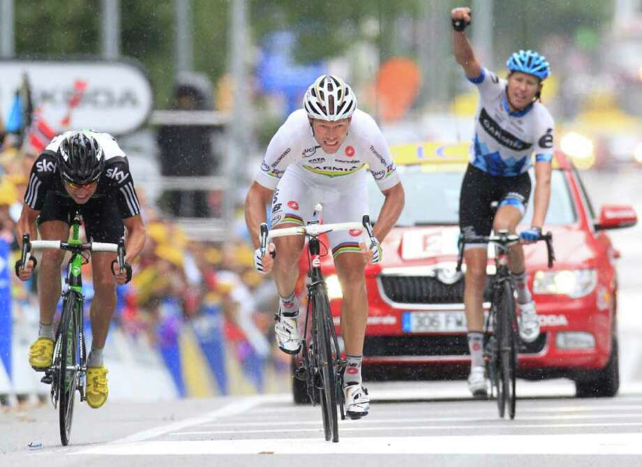 Teammate Ryder Hesjedal of Canada, right, clenches his fist as teammate Thor Hushovd of Norway, center, crosses the finish line to win the 16th stage of the Tour de France cycling race over 162.5 kilometers (101 miles) starting in Saint Paul Trois Chateaux and finishing in Gap, southern France, Tuesday July 19, 2011. Left is Edvald Boasson Hagen of Norway who took second place. (AP Photo/Laurent Rebours) Photo: Laurent Rebours, STF / AP