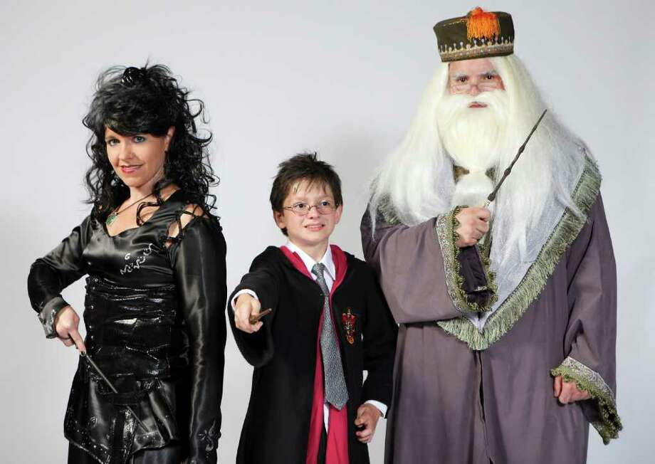 "FOR METRO - Portrait of Brandy Lawson dressed as ""Bellatrix Lestrange""  (from left), Zachary Swygart, 12, dressed as ""Harry Potter"" and Jason Lawson dressed as ""Dumbledore"" Thursday July 14, 2011 at the Santikos Palladium. (PHOTO BY EDWARD A. ORNELAS/eaornelas@express-news.net) Photo: EDWARD A. ORNELAS, Eaornelas@express-news.net / © SAN ANTONIO EXPRESS-NEWS (NFS)"
