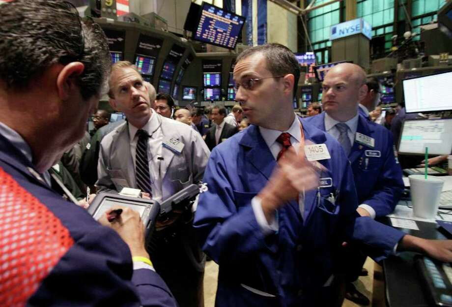 In this July 18, 2011 photo, specialist Neil Gallagher, foreground right, works at his post on the floor of the New York Stock Exchange. Lackluster world stocks got a boost Tuesday, July 19, from an early rebound in Europe and the U.S. as debt worries that have shadowed both regions in recent days kept Asian markets largely in check. (AP Photo/Richard Drew) Photo: Richard Drew, STF / AP