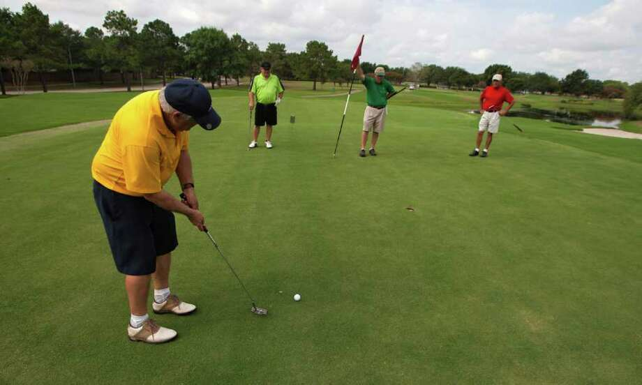 7/18/2011: Scott Dennis puts , as, , from left to right, Terry Hatrick, Sonny Lyons and Gene Meyers watch on the 12th hole at the Golf Club at Cinco Ranch on July 18, 2011. The Golf Club at Cinco Ranch in Katy Texas closed its door on May 7, 2011 to replace all its greens. The course reopened it doors on July 17, 2011.  Special to the Chron: Thomas B. Shea Photo: Special To The Chron: Thomas B., 750 / Special to the Chron: Thomas B. Shea