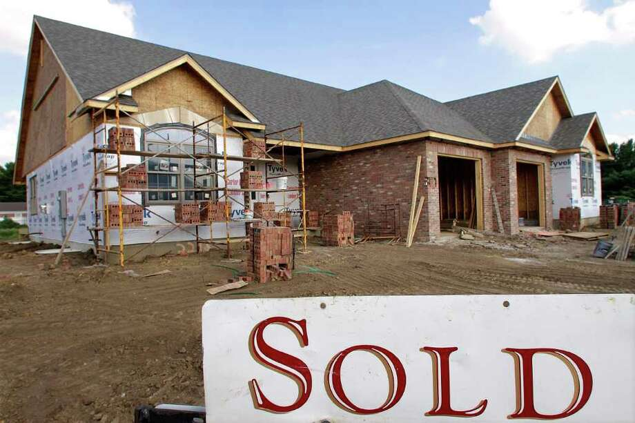 In this photo taken July 14, 2011, a SOLD, newly constructed home is shown in Springfield, Ill. Builders broke ground on more single-family homes and apartments in June, as the home-building industry tried to shake off a historically bad spring.(AP Photo/Seth Perlman) Photo: Seth Perlman, STF / AP