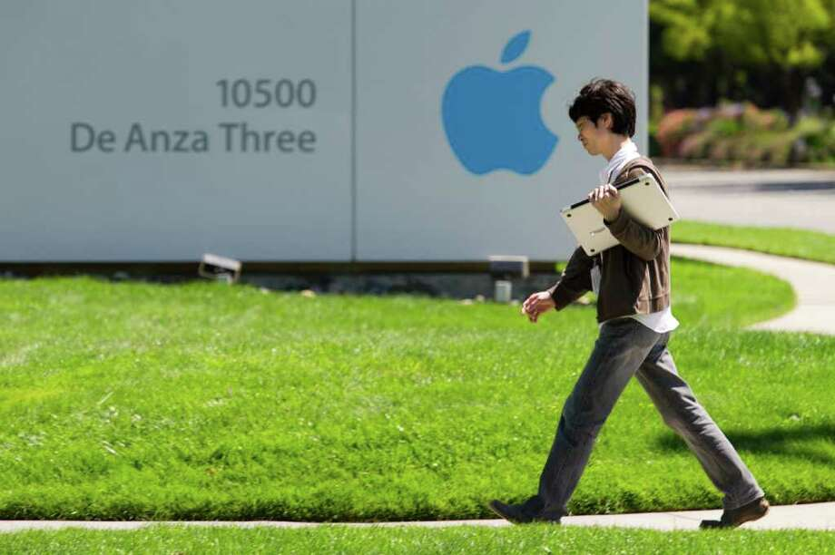 A man walks past an Apple Inc. sign at company headquarters in Cupertino, California, U.S., on Friday, July 15, 2011. Apple Inc. is set to post a 69 percent jump in quarterly profit when it reports results today, after record buying of the iPad and Mac computer made up for weaker demand for its aging iPhone 4. Photographer: David Paul Morris/Bloomberg Photo: David Paul Morris, 877614 / © 2011 Bloomberg Finance LP