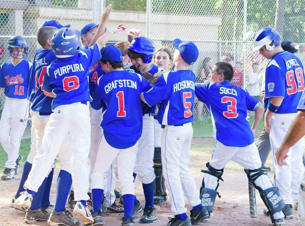 North Stamford greets Alex Mella at home plate after he hit a homer as the team works its way to defeating National Lione 9-5 in the Little League District 1 Championship at Scalzi Park in Stamford, Conn., July 17, 2011.