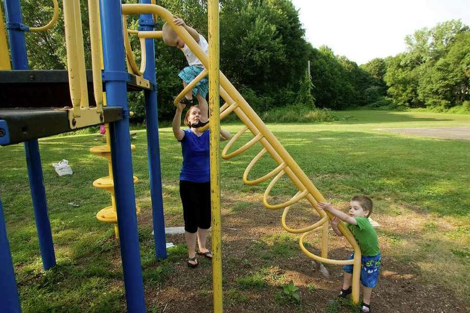 Wendy Miller, of Danbury, helps her son, David Miller, 3, step down from playground equipment, as David's twin brother, Benjamin, goes up at Highland Avenue Park on Tuesday, July 19, 2011.  The city wants to build a dog park in the rear of the park, top right, but Miller worries about dogs being near children. Photo: Jason Rearick