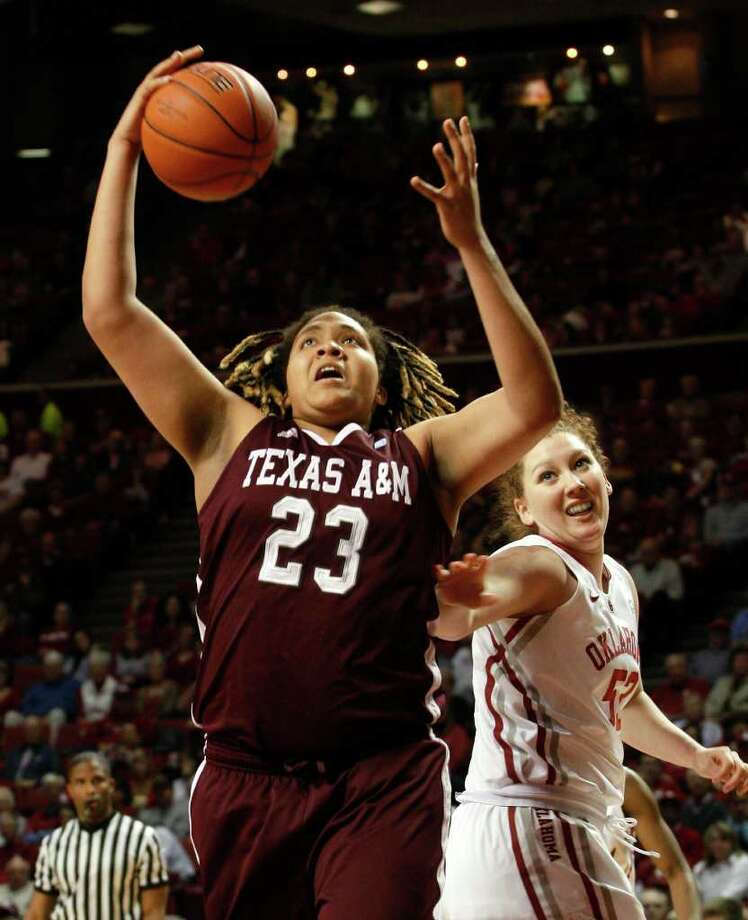 Texas A&M center Daniell Adams rebounds next to Oklahoma's Joana McFarland in a January game in Norman, Okla. Adams led A&M to its first national title in April. Photo: Bill Waugh/Associated Press