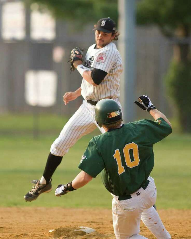 Danbury's Dillon Everett, despite having to leap for a high throw, comes down in time to catch the Sanford Mainers' Paul Kronenfeld trying to steal Tuesday night at Rogers Park. Photo: Barry Horn