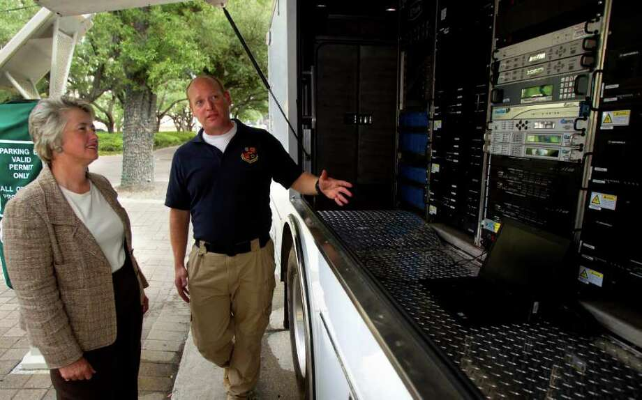 Mayor Annise Parker (left) listens as Sprint Emergency Response Team Network Engineer Brian Hudnet (right) explains the funcionality of a Nextel SATCOLT, a Satellite Cellsite on Light Truck, owned by Sprint outside of City Hall Monday, July 18, 2011, in Houston. The mobile cell site on wheels is a self-contained satellite truck that can provide 360 degree coverage up to a 3-5 mile radius. The vehicle holds 160 gallons of fuel that allows it to be deployed for up to 10 days before needing to refuel. Currently using At&t the City of Houston is looking to possibly change contracts for their emergency communication carrier for use during weather events and or disasters. ( Cody Duty / Houston Chronicle ) Photo: Cody Duty, Staff / © 2011 Houston Chronicle