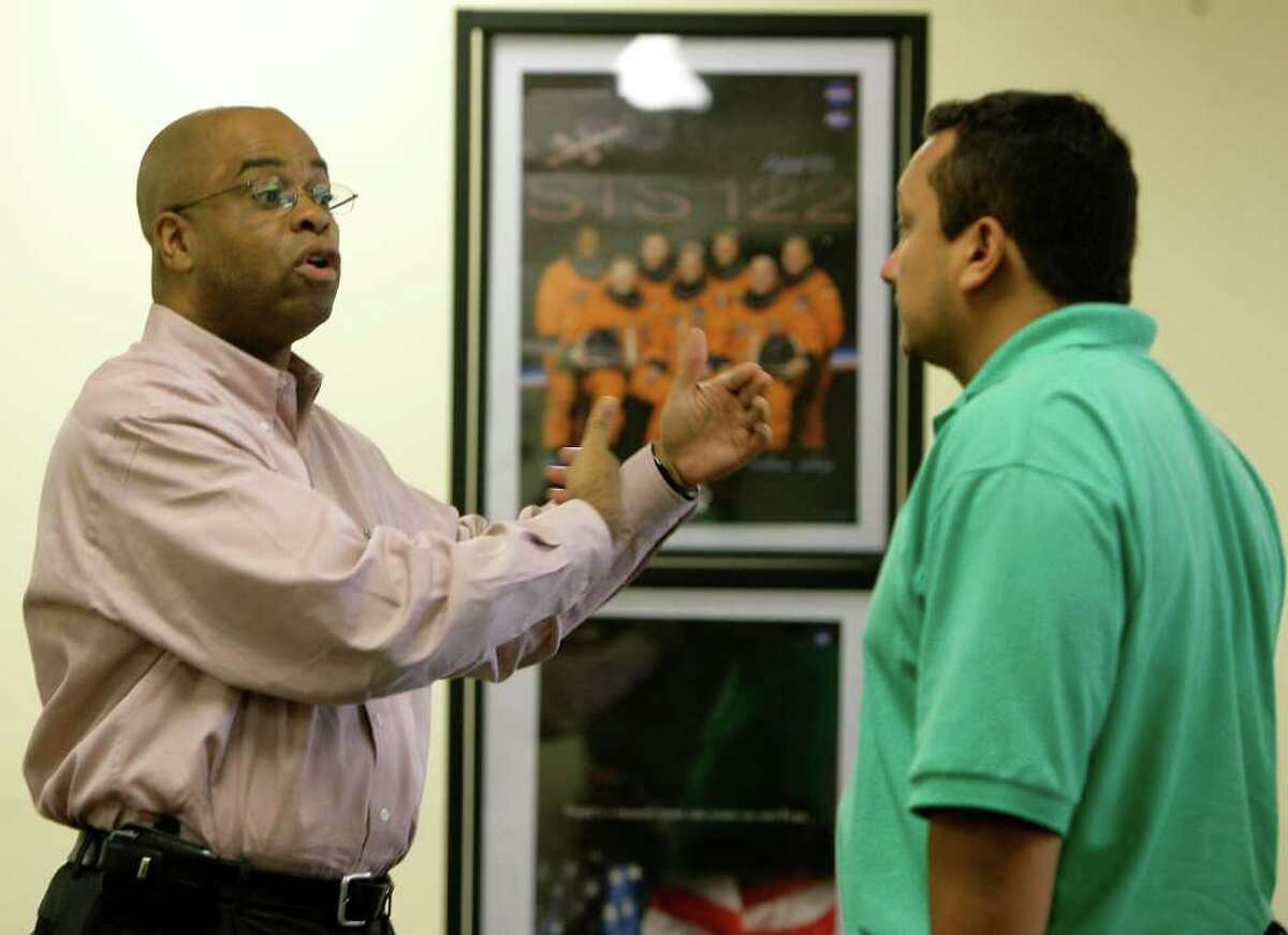 Astronaut memorabilia line the walls of the Aerospace Transition Center as Financial Aid Specialist Valentino Murphy (left) talks with job seeker David Quinones (right) Monday, July 18, 2011, in Houston. Located three miles from Johnson Space Center, the center is designed help thousands of aerospace workers find another job. ( Cody Duty / Houston Chronicle )