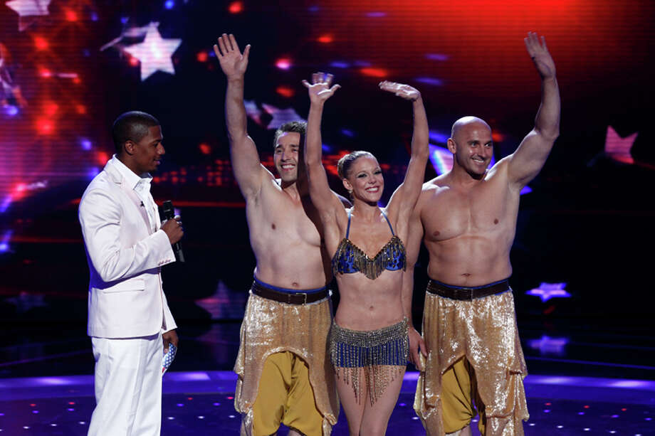 "Cassie Sandou, flanked by husband Konstantin Sandou, left, and his brother Sergei get the word from host Nick Cannon that they have advanced on ""America's Got Talent."" NBC"