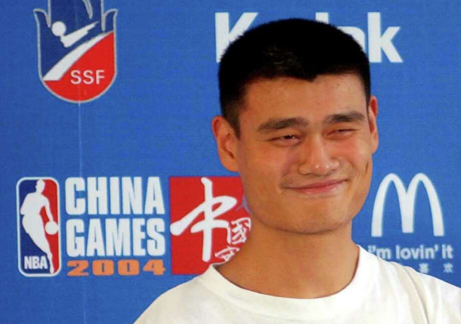 FILE - In this Oct. 13, 2004, file photo Houston Rockets' Yao Ming answers questions from journalists during a press conference for the NBA China 2004 game in Shanghai, China. Yao Ming should make it official on Wednesday July 20, 2011, announcing what is widely expected to be his retirement from the NBA and a sport that made him a household name in China. (AP Photo/Eugene Hoshiko, File) Photo: EUGENE HOSHIKO, STF