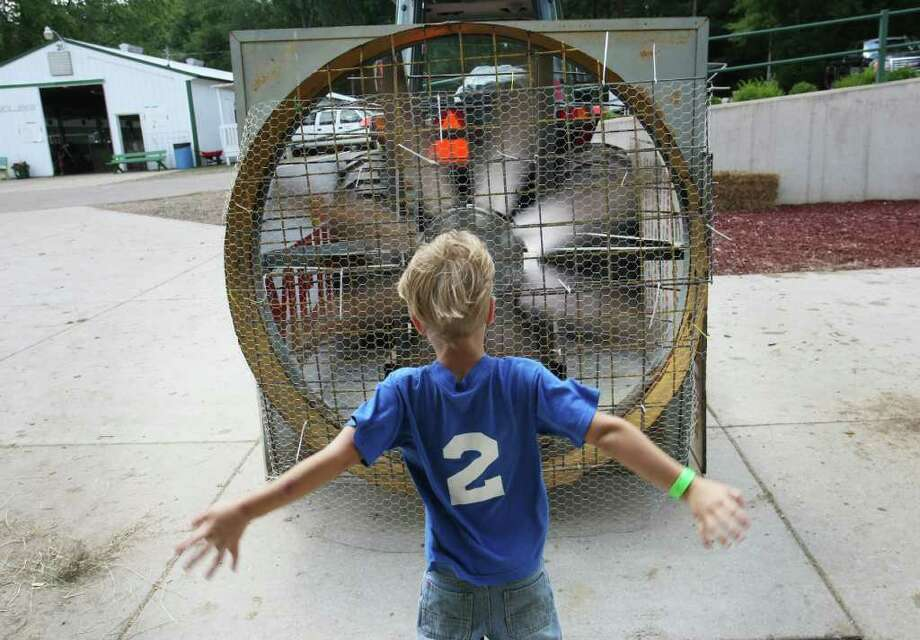 Luke McCrory, 5, from Coopersville, cools off in front of a giant fan at the Berlin Fair in Marne, Mich., Tuesday, July 19, 2011. (AP Photo/The Grand Rapids Press, Cory Morse) Photo: Cory Morse, MBR / The Grand Rapids Press