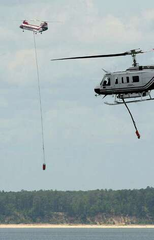 Helicopters shuttle tons of water from the Sam Rayburn Reservoir to a nearby fire that claimed more than 3,500 acres of forest in June. Texas Forest Service doesnít have any of its own aircraft so they federal and ëcall when neededí contracts with folks across the country. The contracts generally include the aircraft, pilot and sometimes a mechanic and fuel truck. The planes and pilots must be credentialed by the US Forest Service in order to work on fires. Guiseppe Barranco/The Enterprise     On good days, weíve had as few as two helicopters working on fires.   Guiseppe Barranco/The Enterprise Photo: Guiseppe Barranco