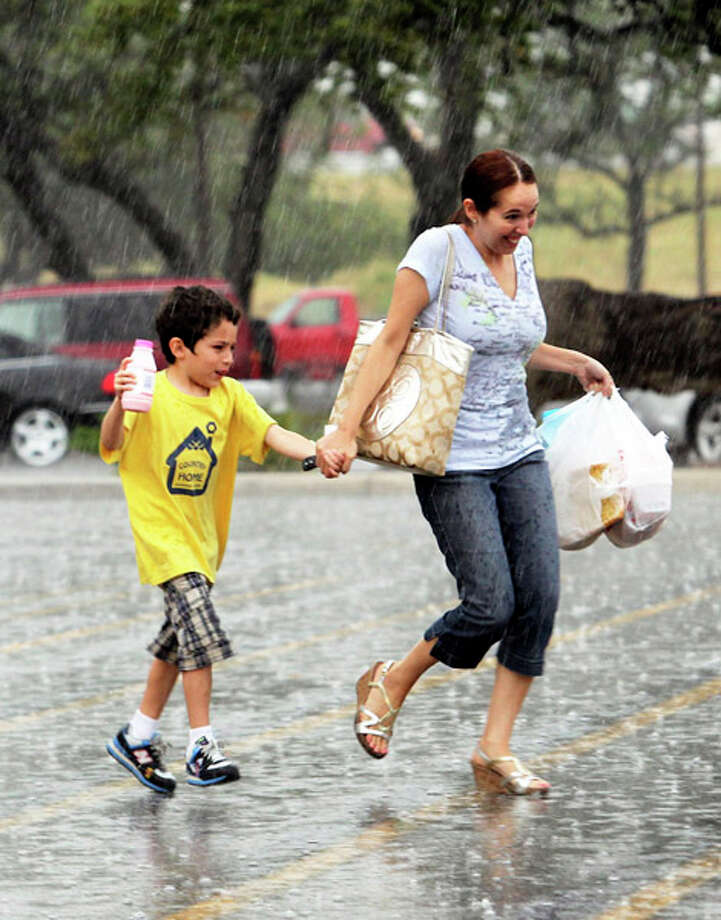A surprise rain shower catches shoppers Michelle and Xander Reyes as they scamper back to their car at the Fiesta Trail H.E.B. at De Zavala and IH-10 on San Antonio's Northwest Side on July 19, 2011. Photo: TOM REEL / treel@express-news.net