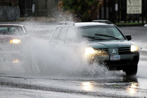 Motorists drive through high water on West Nakoma Drive as storms hit the San Antonio area on July 19, 2011. Photo: ANDREW BUCKLEY / abuckley@express-news.net