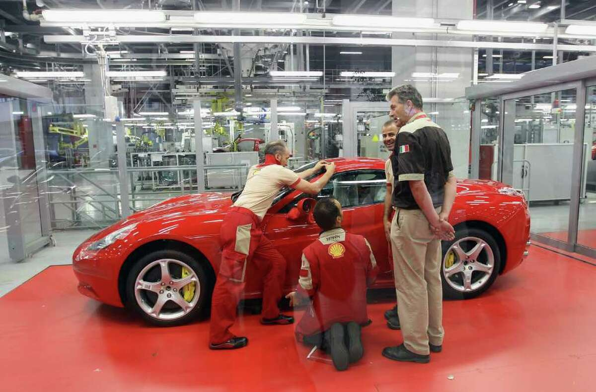 MARANELLO, ITALY - JULY 19: Employees work in the Nuovo Montaggio Vetture (New Cars Assembly) department during a Ferrari factory tour on July 19, 2011 in Maranello, Italy. Ferrari S.p.A. is an Italian manufacture based in Maranello and founded by Enzo Ferrari in 1929. (Photo by Vittorio Zunino Celotto/Getty Images)