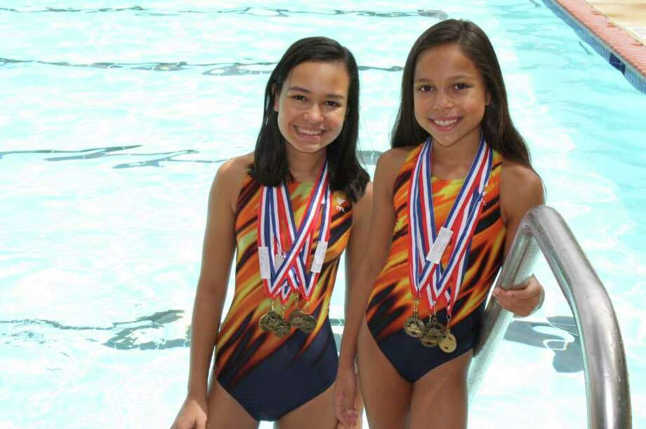 Sisters Camryn (left) and Peyton Hummel, representing the Finesilver Ranch Torpedoes, each collected the maximum five gold medals at the Lonestar Summer League Championships held June 26 at the Josh Davis Natatorium. Both were high point winners in their age groups. Photo: Courtesy