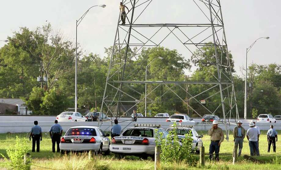 Police wait for a man to climb down from an electrical tower in Houston. Cody Duty/Houston Chronicle / © 2011 Houston Chronicle
