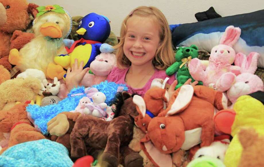 Morgan Sellers, 7, of Rosharon sits with a few of the approximately 500 stuffed animals she plans to send to Joplin, Missouri, in the next few weeks for the children impacted by the EF-5 tornado that leveled parts of the city in May. Morgan is worried children are not sleeping well at night because they do not have a stuffed animal to cuddle with when going to sleep. Photo: Christy Wooten