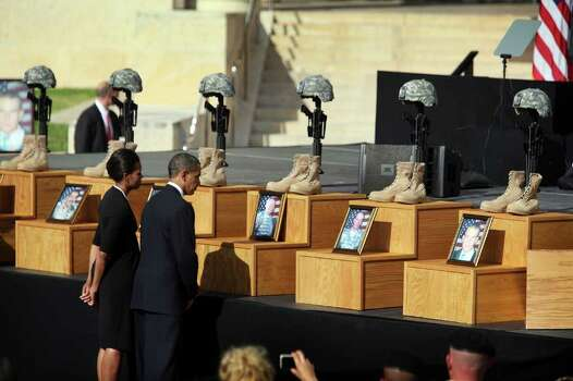 FORT HOOD, TX - NOVEMBER 10:  U.S. President Barack Obama (R) and first lady Michelle Obama pay their respects to the people killed as they attend a memorial service for the thirteen victims of the shooting rampage allegedly by U.S. Army Major Nidal Malik Hasan on November 10, 2009 in Fort Hood, Texas. Hasan, an army psychiatrist, is accused of killing 13 people and wounded 30 during a shooting at the military base. Photo: Joe Raedle, Getty Images / 2009 Getty Images