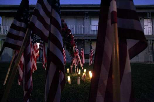 FOR METRO - A memorial for the Fort Hood shooting that consist of thirteen American flags and flowers in the Casa Del Norte apartments where Maj. Nidal Malik Hasan lived Monday Nov. 9, 2009 in Killeen, Tx. PHOTO BY EDWARD A. ORNELAS/eaornelas@express-news.net) Photo: EDWARD A. ORNELAS, SAN ANTONIO EXPRESS-NEWS / eaornelas@express-news.net