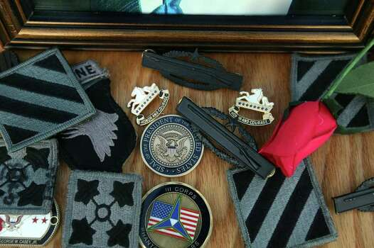 FORT HOOD, TX - NOVEMBER 10: The Presidential coin that President Barack Obama placed is seen among other momentos placed in front of photographs of those killed during the memorial service in honor of the 13 victims of the shooting rampage allegedly by U.S. Army Major Nidal Malik Hasan, on November 10, 2009 in Fort Hood, Texas. Hasan, an army psychiatrist, is accused of killing 13 people and wounding 30 in a shooting at the military base on November 5, 2009. Photo: Joe Raedle, Getty Images / 2009 Getty Images