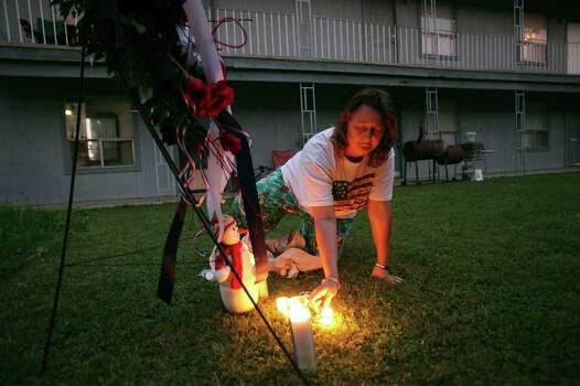 FOR METRO - A neighbor (who did not want to be identified) of Maj. Nidal Malik Hasan lights a candle near a wreath in the Casa Del Norte apartments  Saturday Nov. 7, 2009 in Killeen, Tx. PHOTO BY EDWARD A. ORNELAS/eaornelas@express-news.net) Photo: EDWARD A. ORNELAS, SAN ANTONIO EXPRESS-NEWS / eaornelas@express-news.net