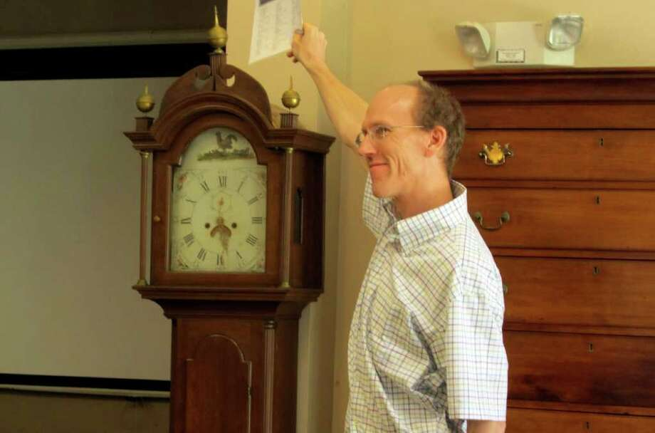 During a recent auction at Fairfield Auction's new location in Monroe, Jack DeStories stands beside a clock, which once belonged to Pulitzer prize-winning author, William Styron. The item sold for $2,200. Photo: Stephanie Paulino