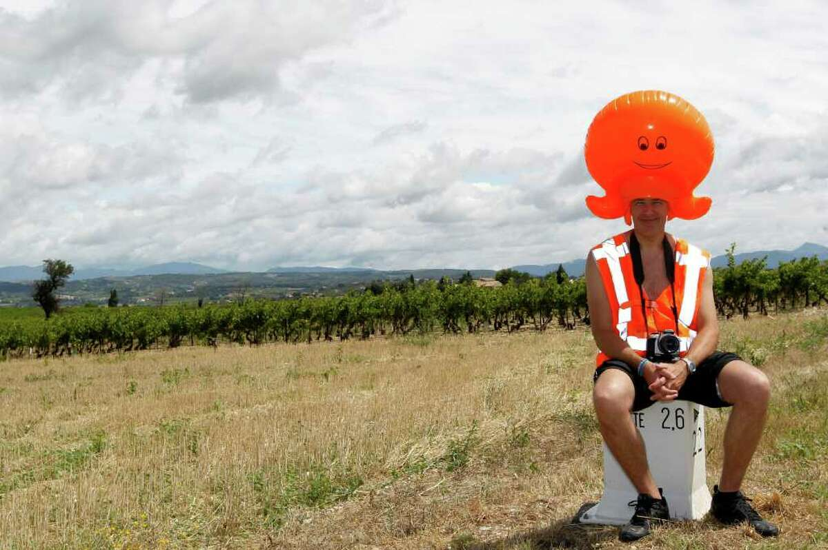A Dutch fan poses with an orange plastic octopus decoration in front of vineyards as he waits for the riders during the 162,5 km and sixteenth stage of the 2011 Tour de France cycling race run between Saint-Paul-Trois-Chateaux and Gap, the principal city of the Hautes-Alpes, southeastern France.