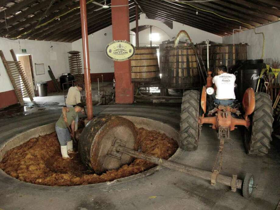This April 2011 photo shows workers at Destileria la Fortaleza, the last distillery in Tequila that still uses a tahona, a giant lava stone, to crush the juices from the baked agave, in Mexico. Here the juice is being pumped into a wooden fermentation vat, where it will spend about a week as the sugar ferments into alcohol.   Tequila consumption has increased 45 percent in the U.S. over the past five years. It's no wonder, then, that the country is waking up to the tourism power of tequila, the drink, and Tequila, the place _ the center of the farming region of the prickly Weber blue agave plants from which the spirit is distilled.   (AP Photo/Tracie Cone) Photo: Tracie Cone, STF / ap