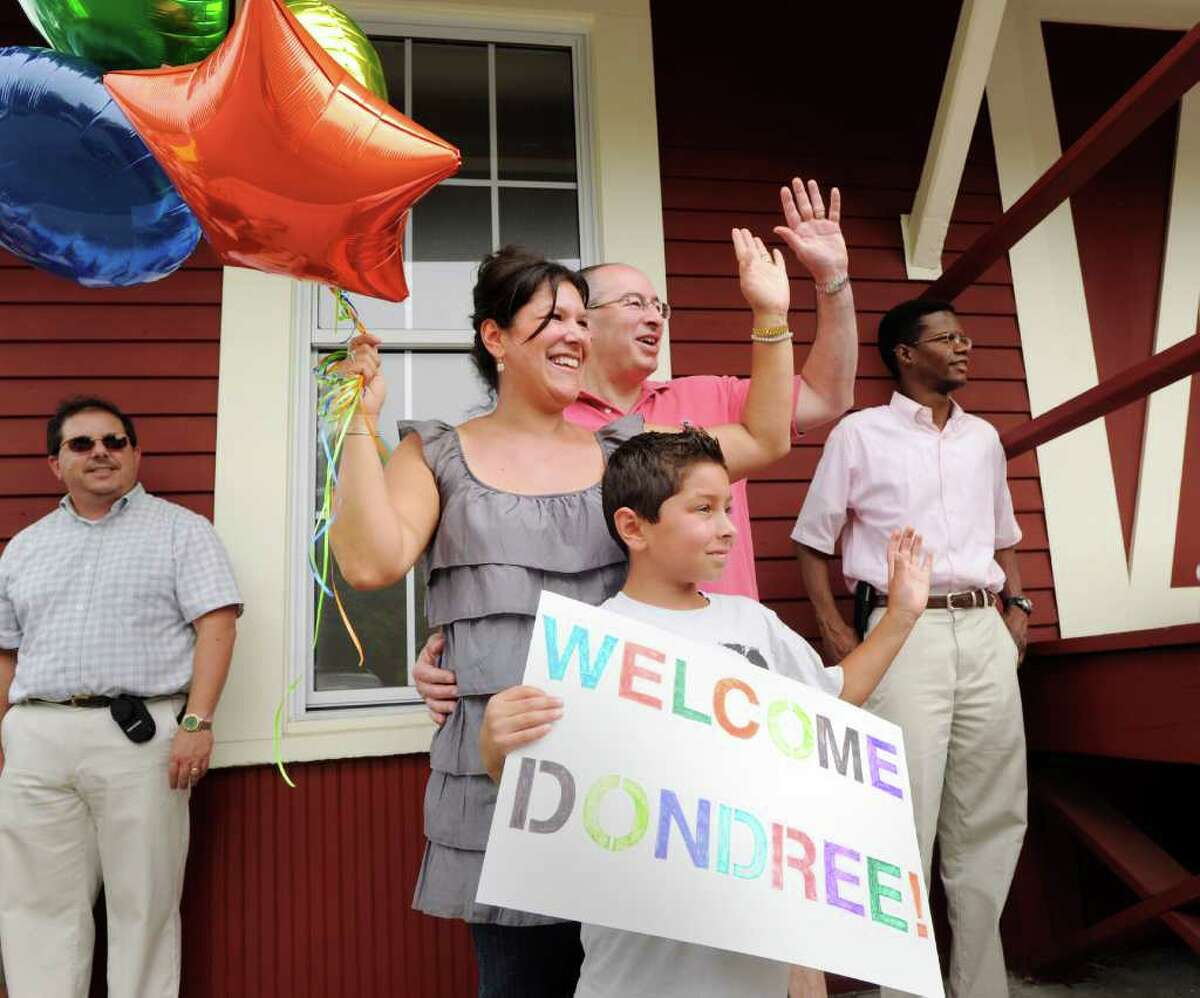 Fresh Air Fund host family Jeffrey and Maritza Block, husband and wife of Greenwich, and their son, Jake, 8, wave as they welcome their arriving Fresh Air Fund kid, Dondree Bell, 9, of Brooklyn, N.Y., during the arrival of Fresh Air Fund kids from New York City at the Old Greenwich train station Friday afternoon, July 8, 2011.