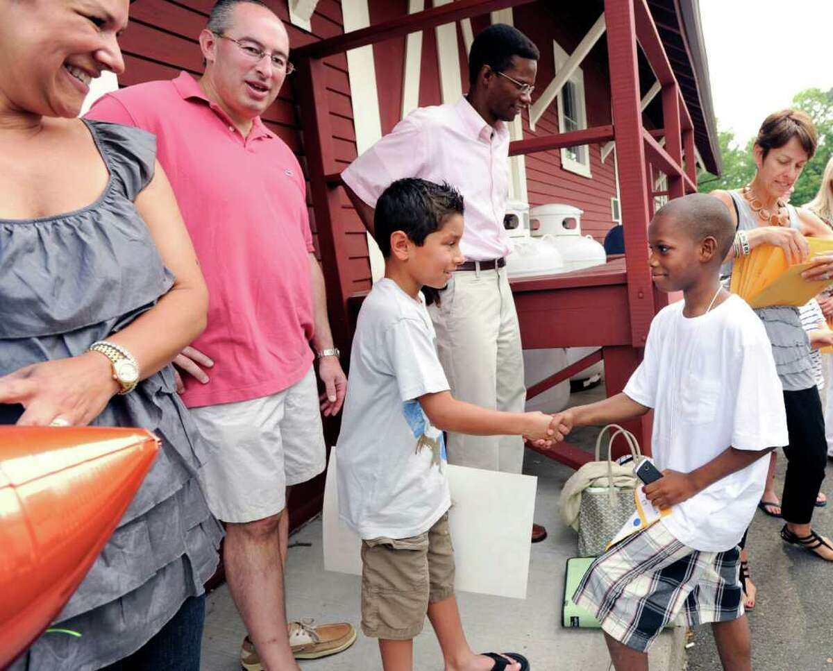 Jake Block, left, 8, of Greenwich, shakes hands with Fresh Air Fund kid Dondree Bell, 9, of Brooklyn, N.Y., during the arrival of Fresh Air Fund kids from New York City at the Old Greenwich train station, Friday afternoon, July 8, 2011. At left are Jake's parents, Maritza and Jeffrey Block. The Block's will be hosting Bell in their home.